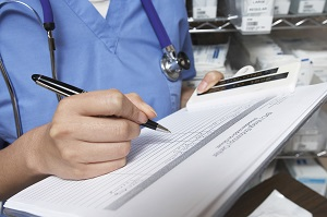 Female doctor writing in patient chart, mid section